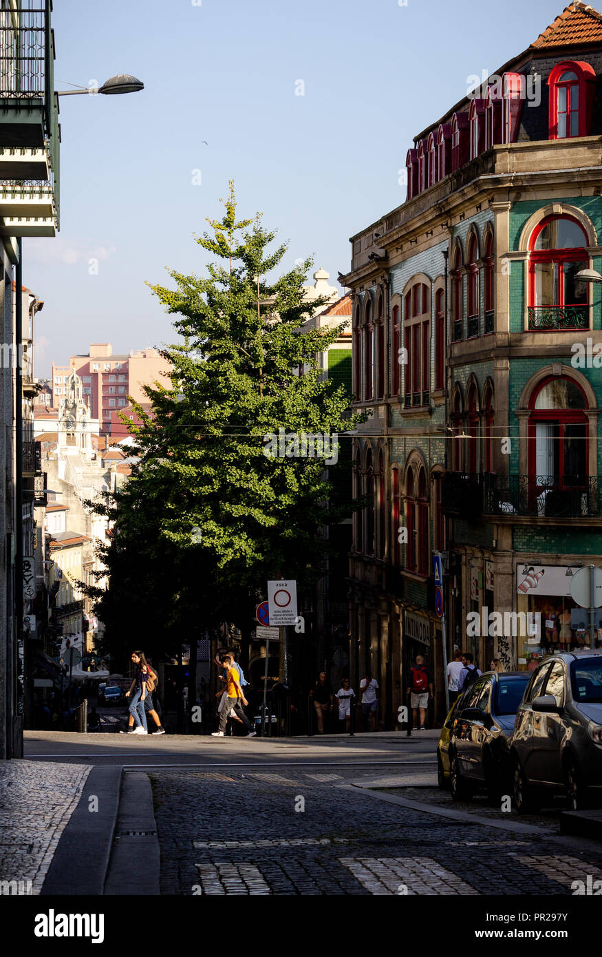 Various people walk in the middle of a street at Porto. - Stock Image