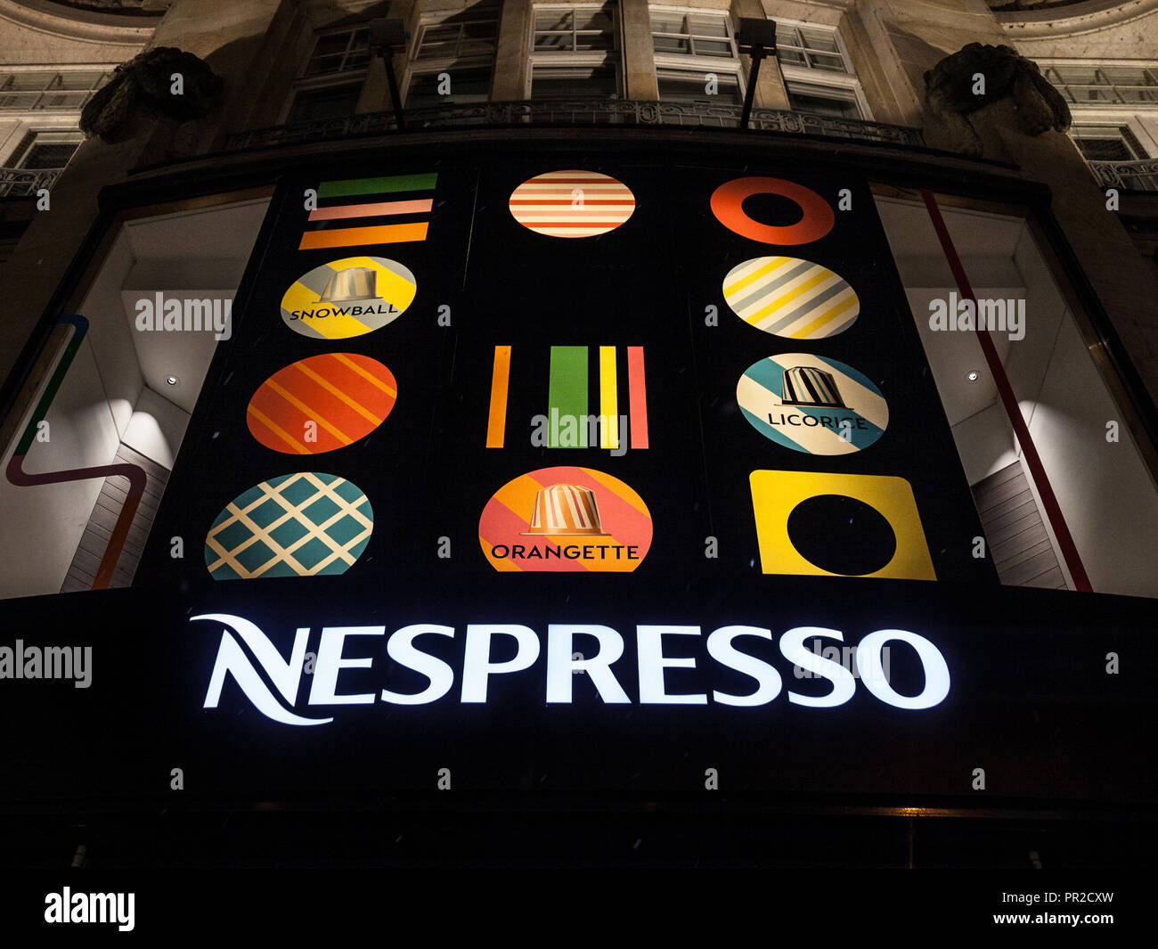 MUNICH, GERMANY - DECEMBER 18, 2017: Nespresso logo on their main shop for Munich at night during snowstorm. Nespresso is the Nestle brand producing e - Stock Image
