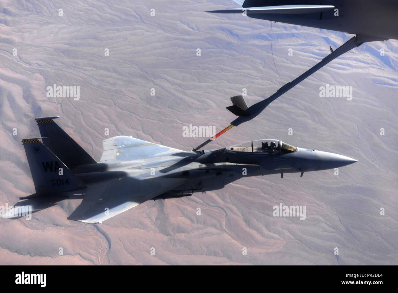 An F-15 fighter jet, assigned to the 433rd Weapons Squadron, at Nellis Air Force Base, Nevada, receives aerial refueling from a KC-135 Stratotanker cargo aircraft assigned to the 509th Weapons Squadron, at Fairchild Air Force Base, Washington, cargo aircraft assigned to the 509th Weapons Squadron, Fairchild Air Force Base, Washington, over the Nevada Test and Training Range July 10, 2017. The United States Air Force Weapons School teaches graduate-level instructor courses that provide the world's most advanced training in weapons and tactics employment to officers of the combat air forces and  - Stock Image