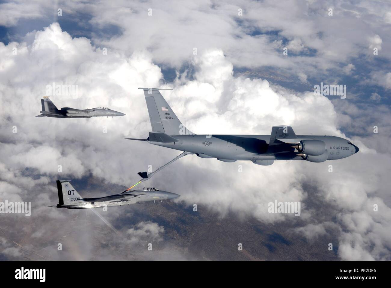 An F-15 fighter jet, assigned to the 433rd Weapons Squadron, at Nellis Air Force Base, Nevada, receives aerial refueling from a KC-135 Stratotanker cargo aircraft assigned to the 509th Weapons Squadron, at Fairchild Air Force Base, Washington, over the Nevada Test and Training Range July 10, 2017. The United States Air Force Weapons School teaches graduate-level instructor courses that provide the world's most advanced training in weapons and tactics employment to officers of the combat air forces and mobility air forces. - Stock Image