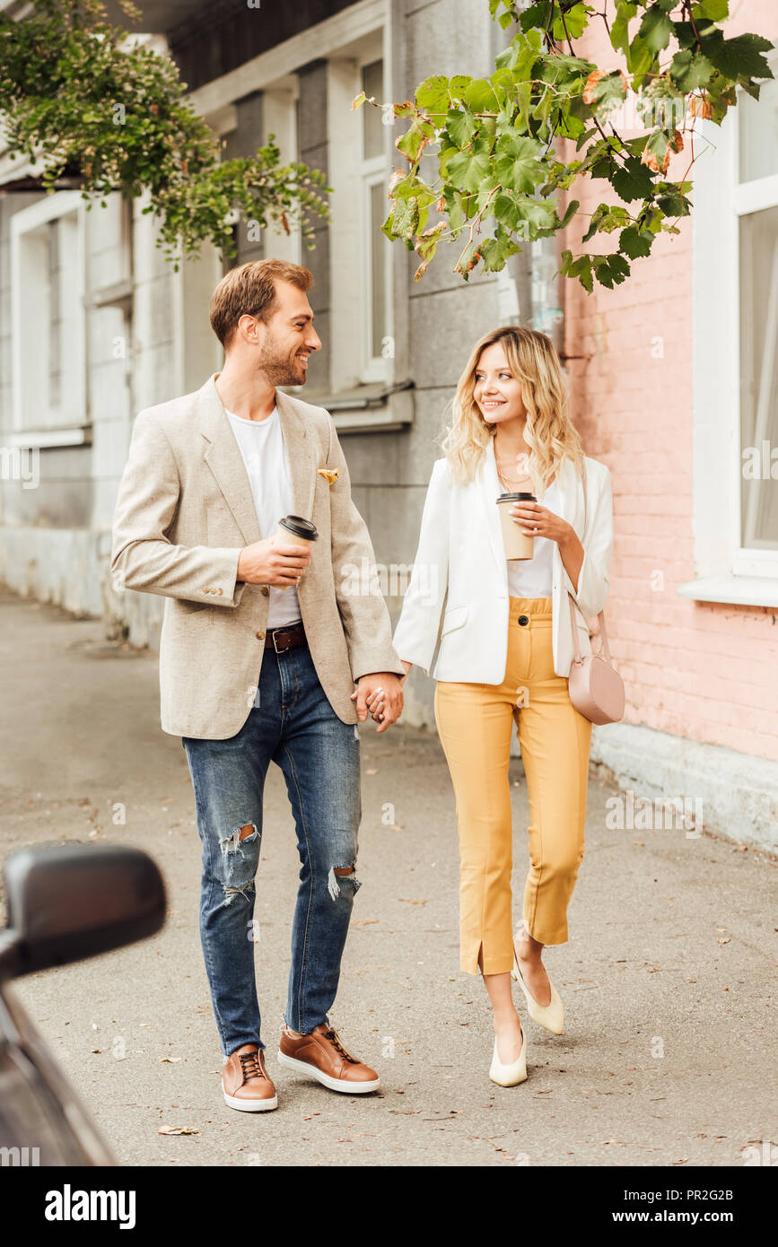 cheerful couple in autumn outfit holding hands, looking at each other and walking on street with disposable coffee cups Stock Photo