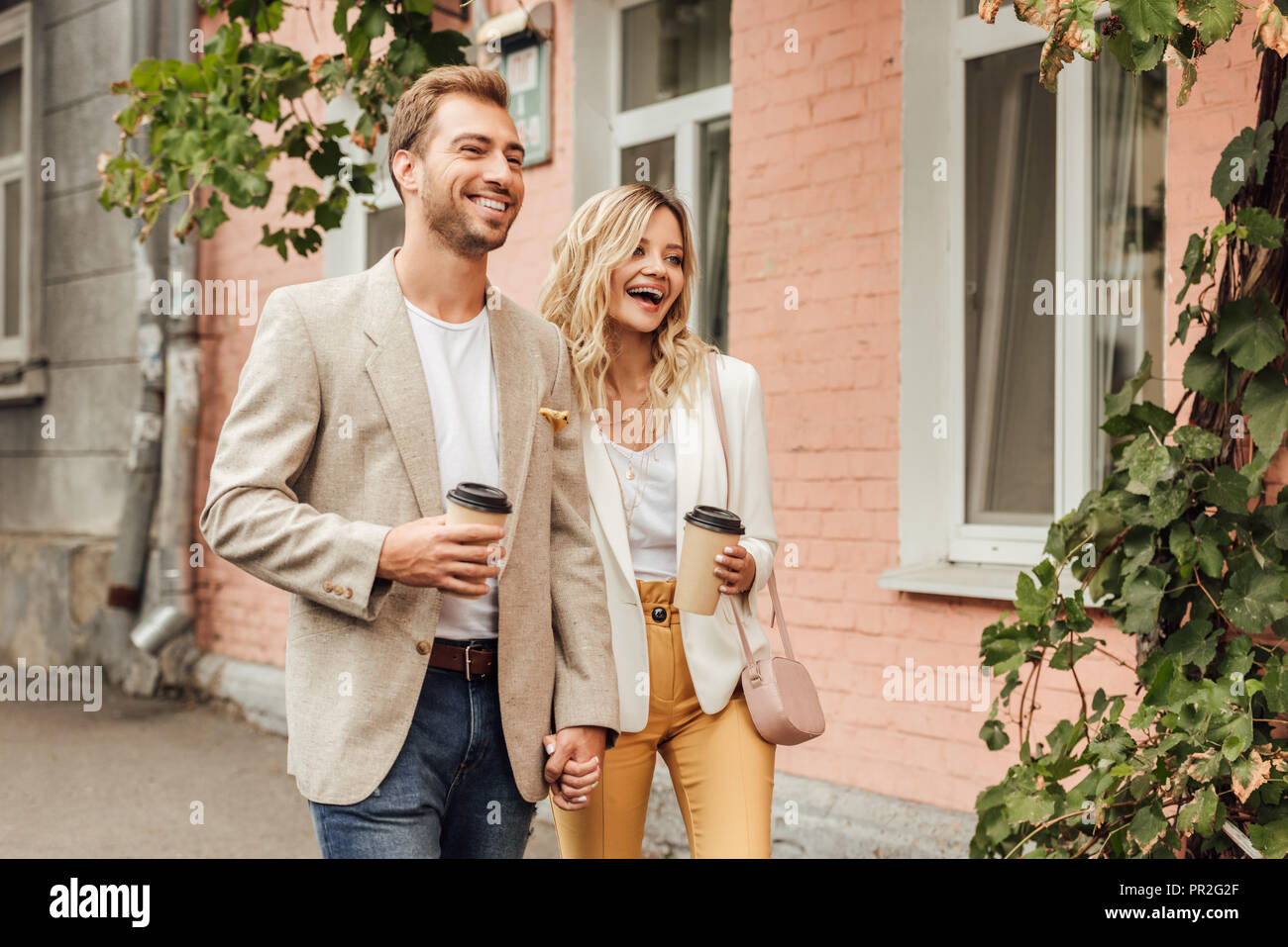 laughing couple in autumn outfit holding hands and walking on street with disposable coffee cups Stock Photo