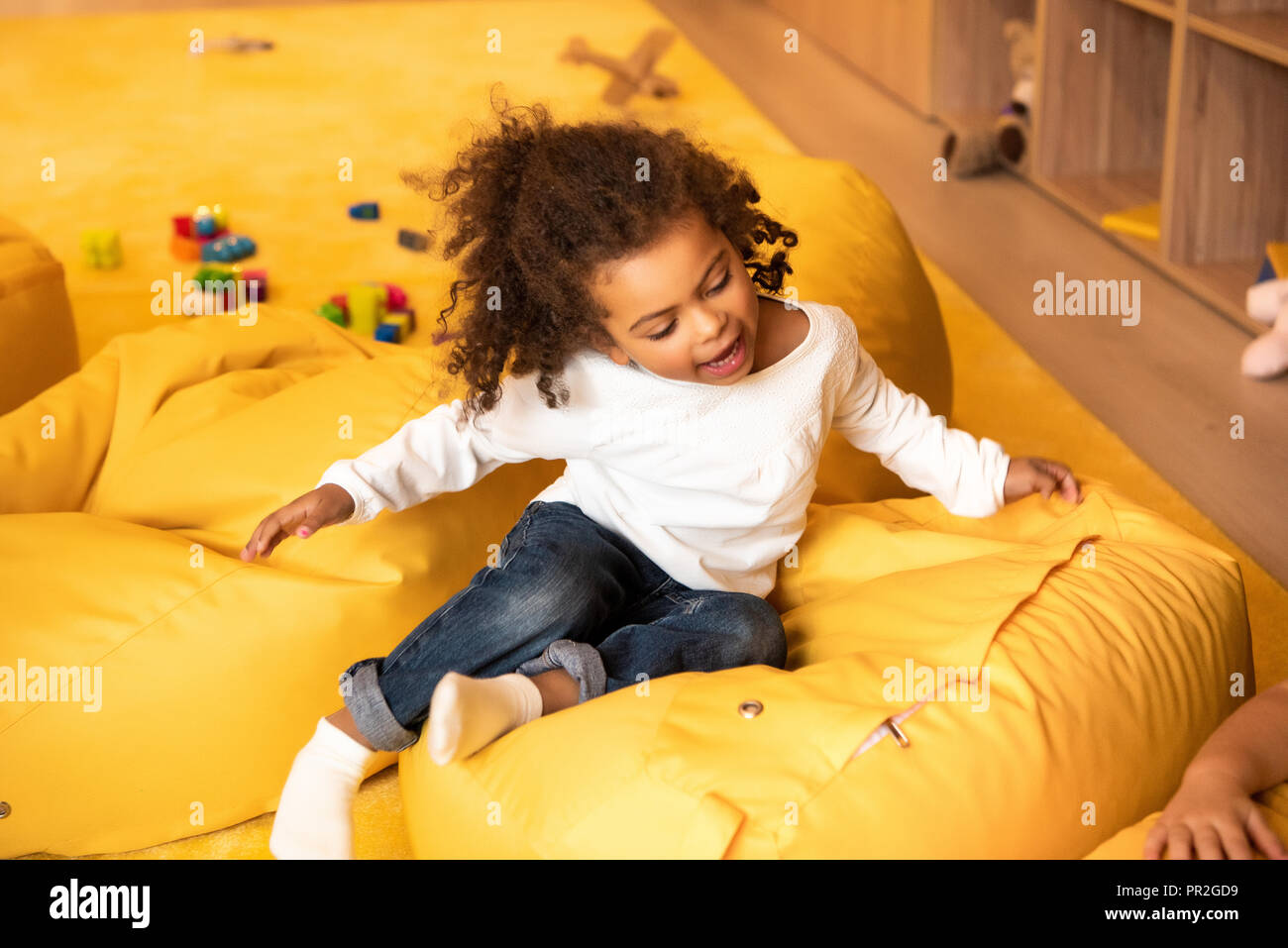 adorable african american kid sitting on bean bag chair in kindergarten - Stock Image