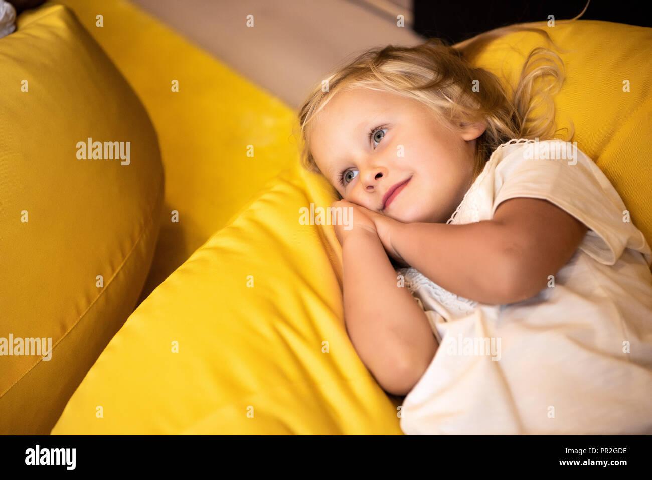 adorable kid lying on bean bag chair in kindergarten - Stock Image