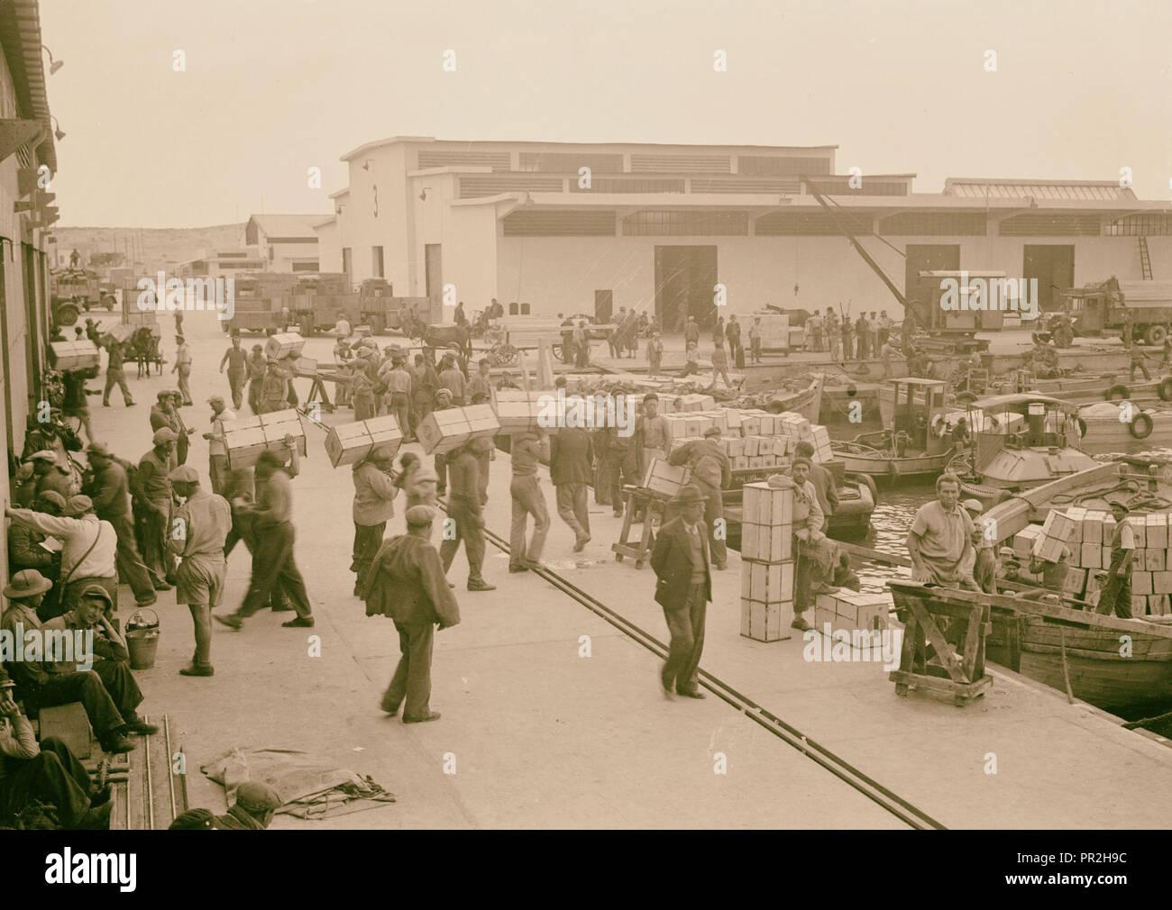 Tel Aviv harbour. A busy scene, loading lighters with orange boxes. 1934, Israel, Tel Aviv - Stock Image