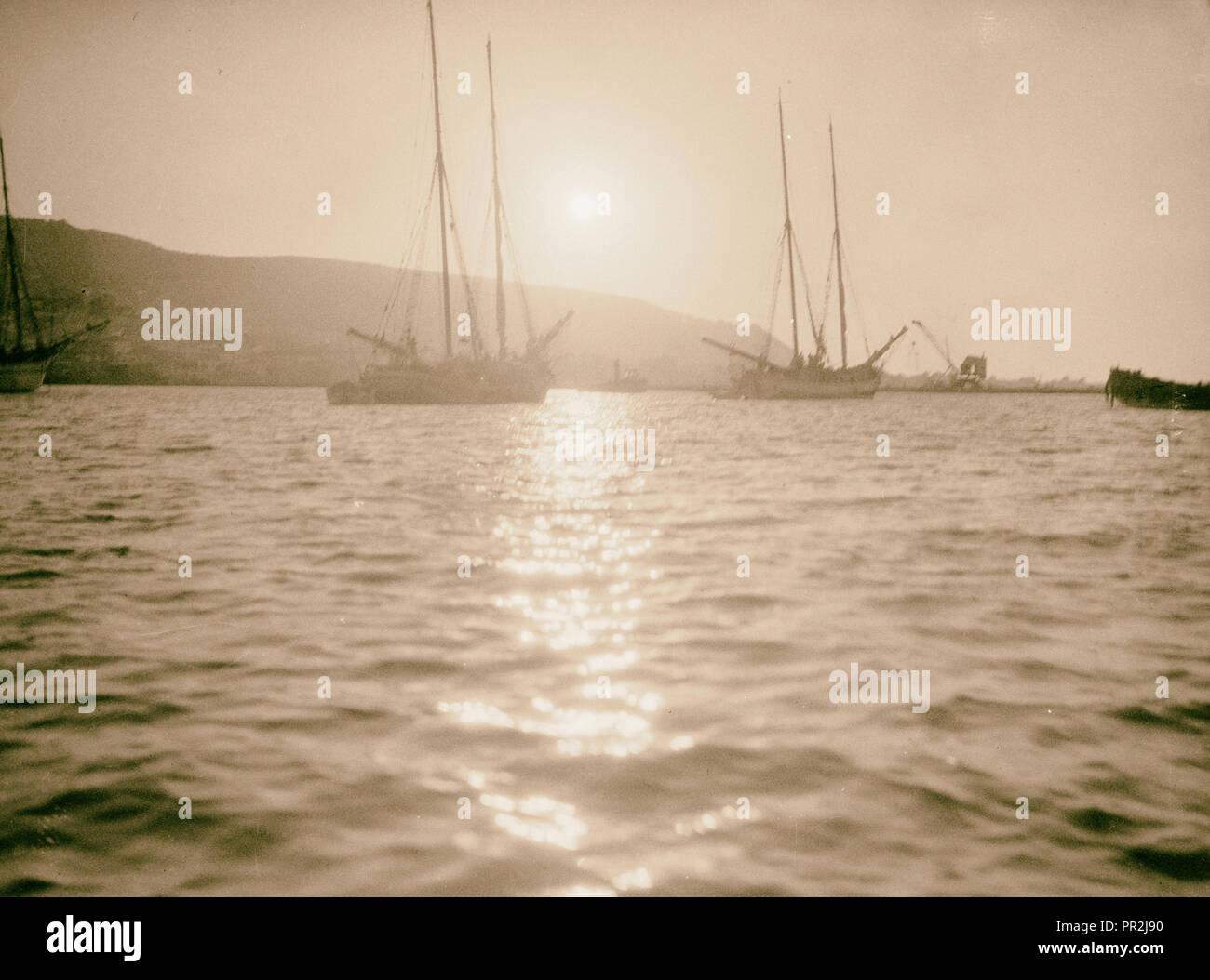 Carmel and Haifa. Carmel at sunset. Tall-masted sailing vessels at anchor. 1920, Israel, Haifa - Stock Image