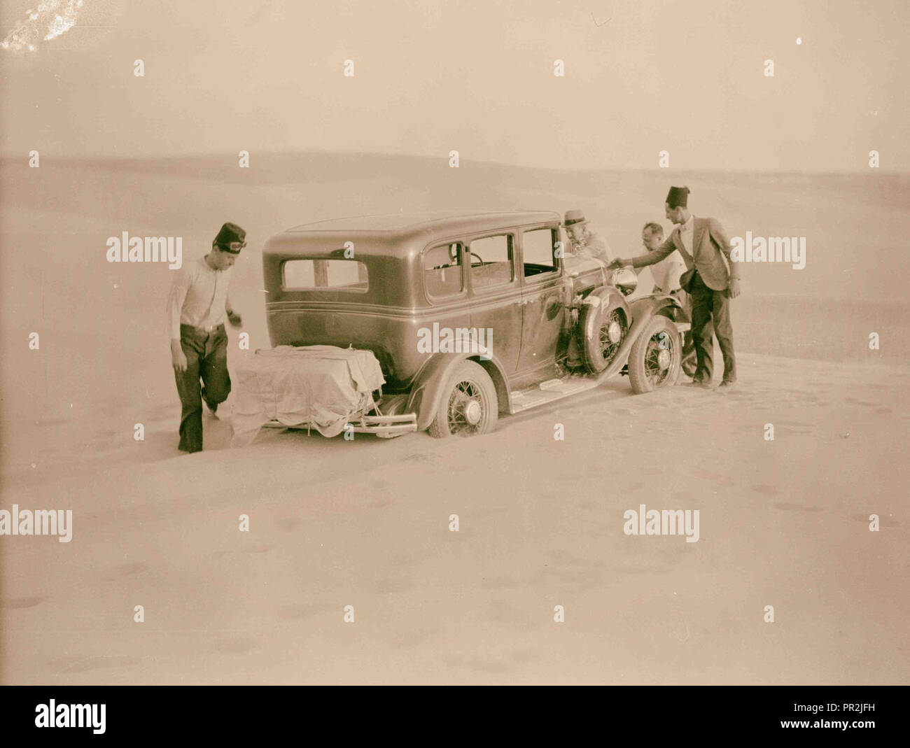 To Sinai by car Car stuck in the midst of a sand dune. Sand drifts across the road. 1920, Middle East, Israel and/or Palestine - Stock Image