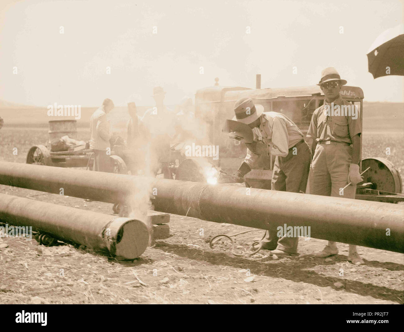 Laying of the Iraq Petroleum Company's pipe line across the Plain of Esdraelon, July 1933. Welding the pipe line. - Stock Image