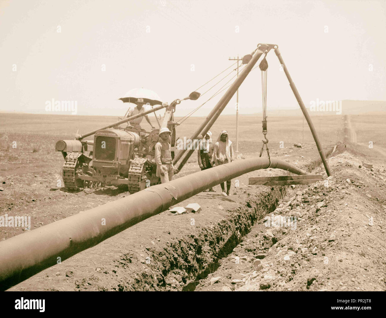 Laying of the Iraq Petroleum Company's pipe line across the Plain of Esdraelon, July 1933. Dropping welded pipe into trench. - Stock Image