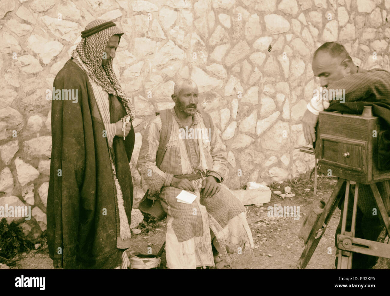 Peasants being photographed for identity cards, headdress removed. Photographer with camera taking a photograph of a man. 1934 - Stock Image