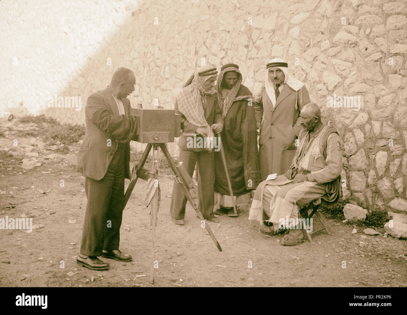 Peasants being photographed for identity cards, headdress removed. Photographer with camera taking a photograph of a man - Stock Image