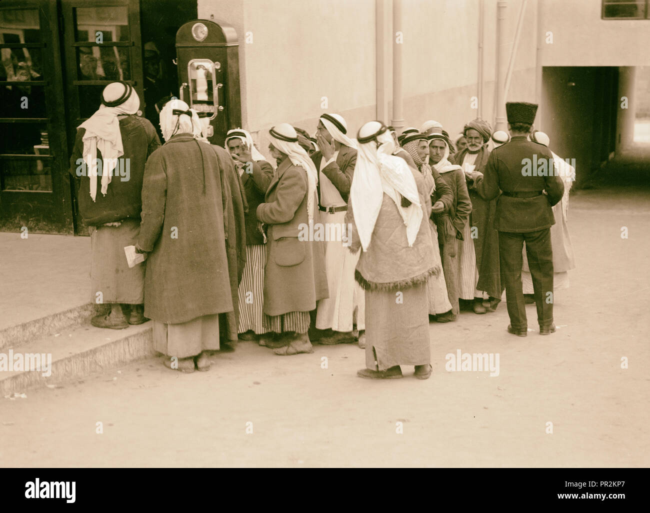 Row of peasants waiting in a queue for identity & pass cards. 1934, Israel - Stock Image