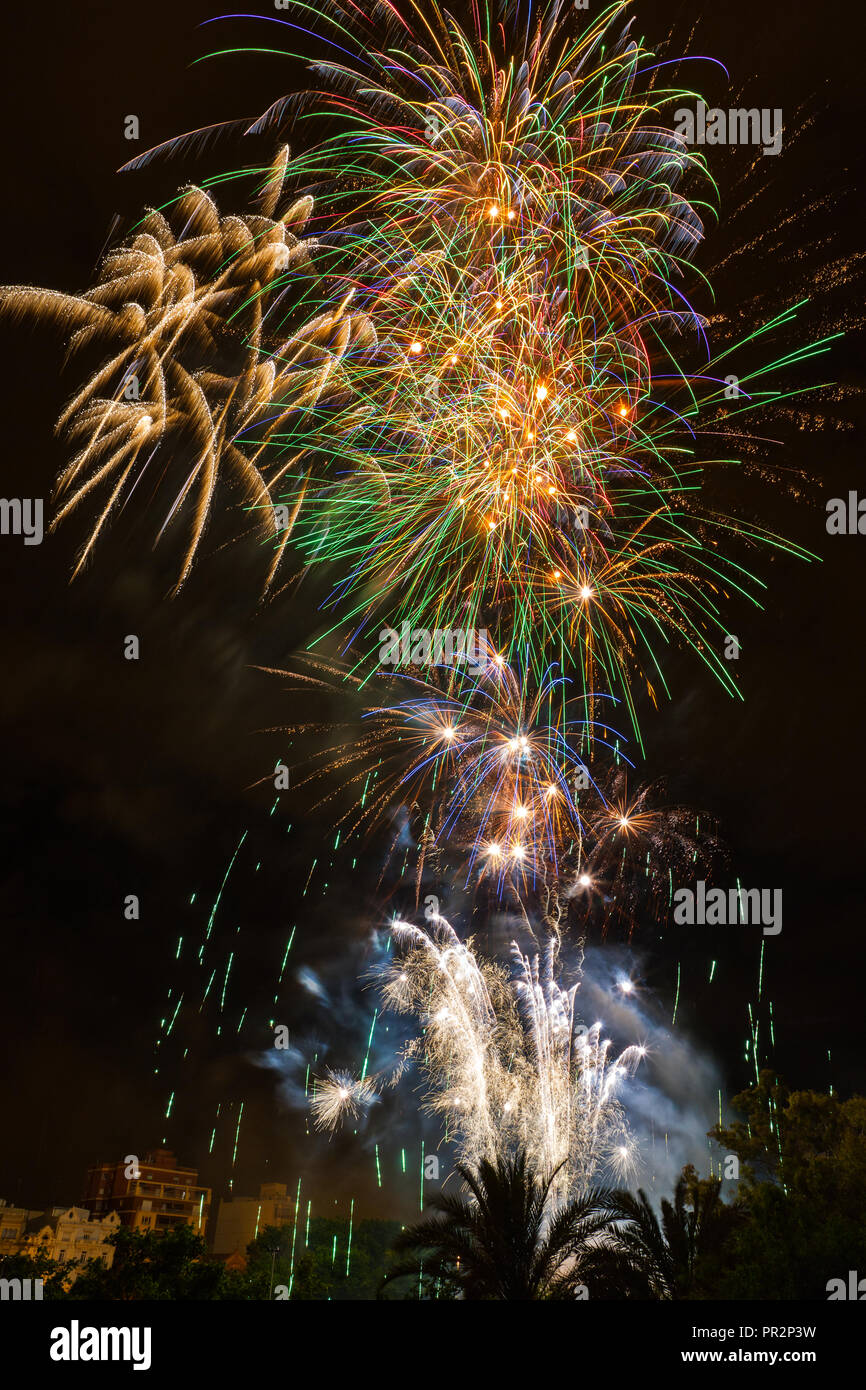 A colorful nighttime fireworks display over the dry riverbed in Valencia, Spain for one of their many pyrotechnic heavy celebrations - Stock Image