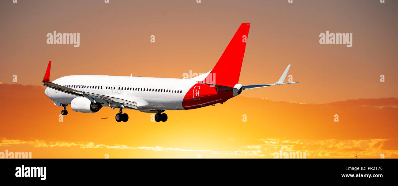A commercial passenger jet flying closeup in a yellow and orange coloured stratus cloud sky. A colourful avation panoramic photo in nature. Queensland - Stock Image