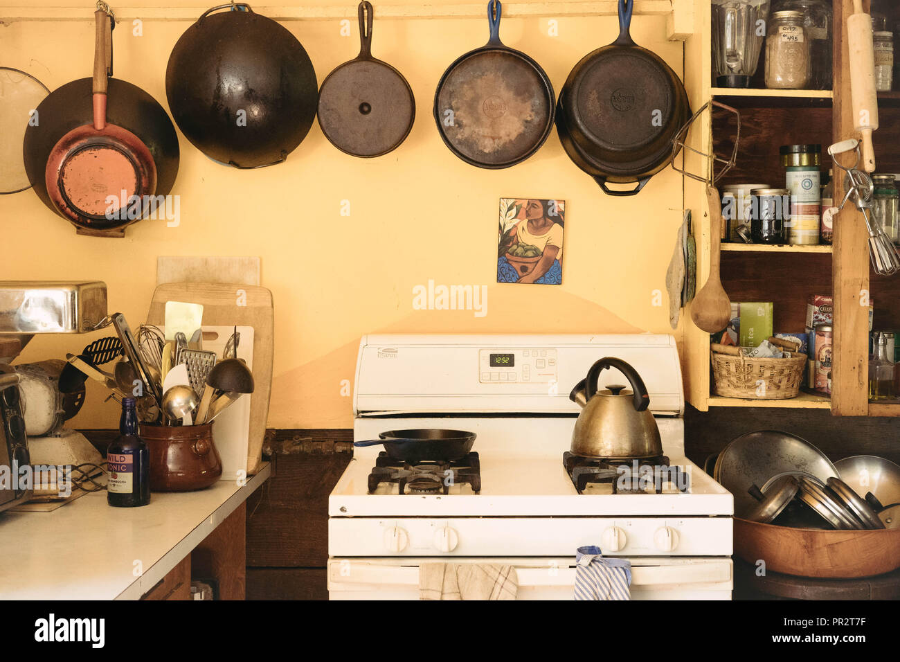 Cast iron cooking pans hanging over a white stove in an old farmhouse kitchen. Kitchen utensils are on each side. - Stock Image