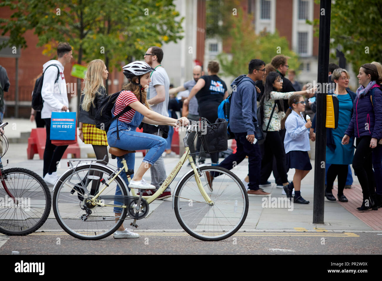 Manchester Oxford Road cycle lane, lady cyclist waiting at red light - Stock Image