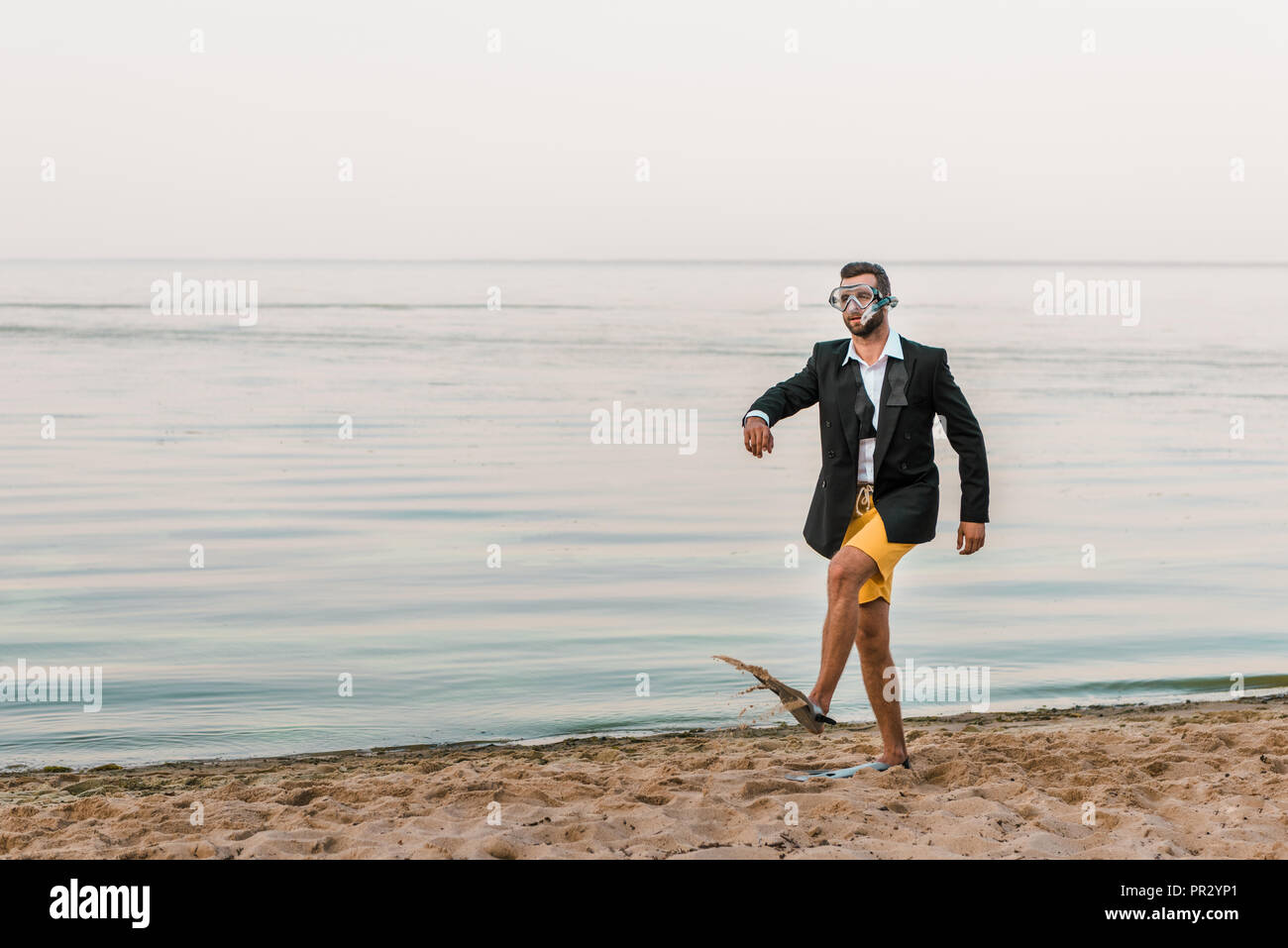 man in black jacket and shorts walking with swimming mask and flippers on sea shore - Stock Image