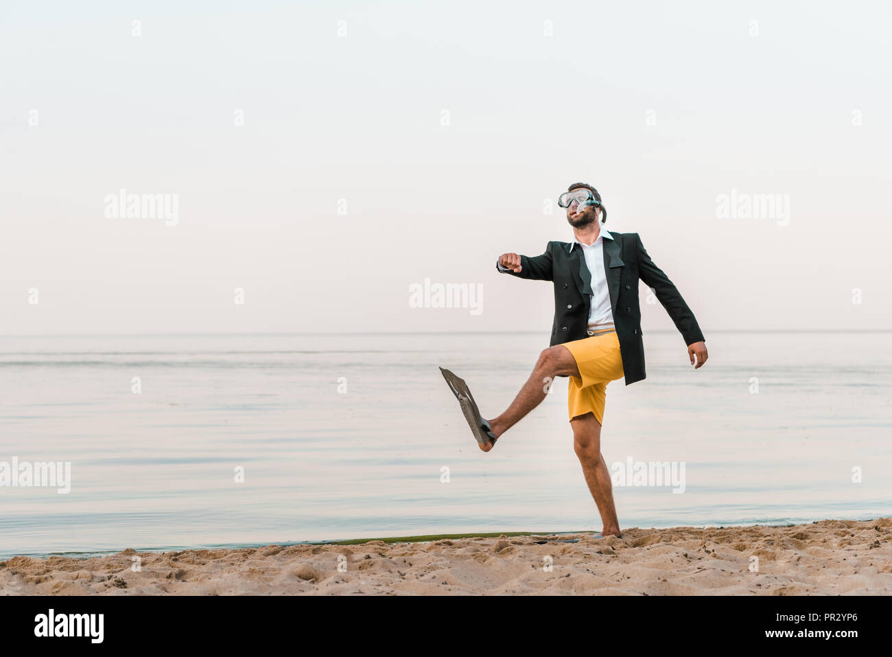 man in black jacket and shorts walking with swimming mask and flippers on sandy beach - Stock Image