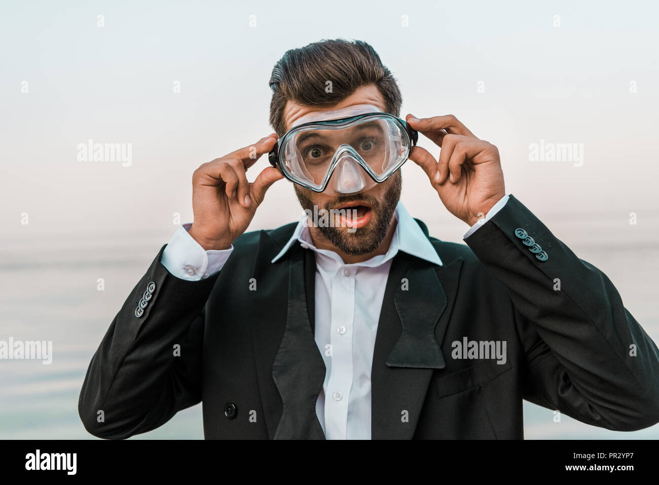 shocked man in black jacket and white shirt touching diving mask near sea Stock Photo