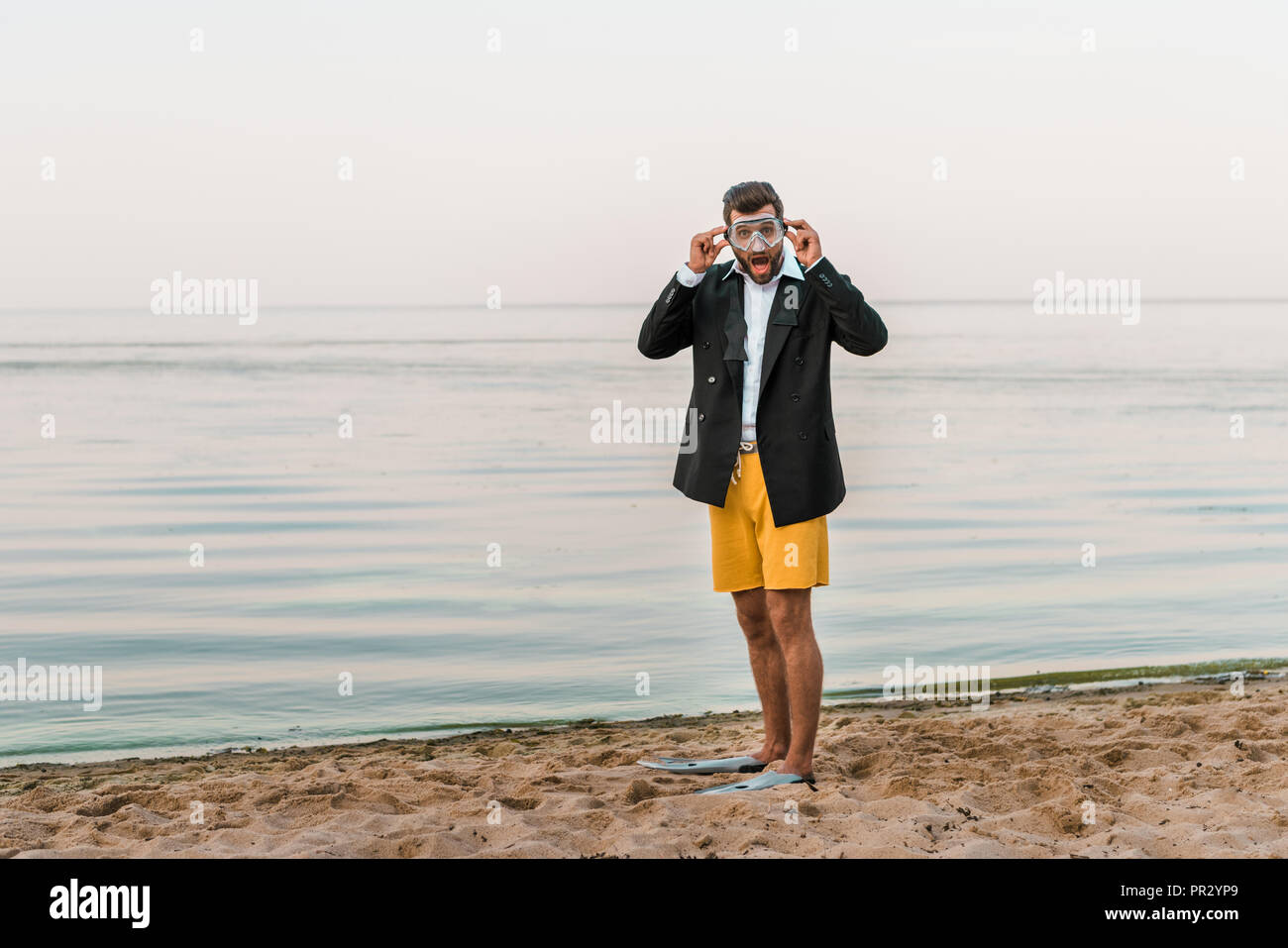 shocked man in black jacket, shorts and flippers wearing swimming mask on beach - Stock Image