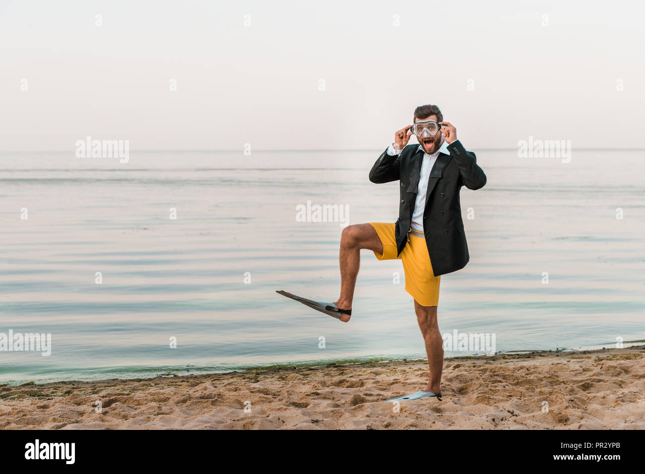 surprised man in black jacket, shorts and flippers touching swimming mask on beach near sea - Stock Image