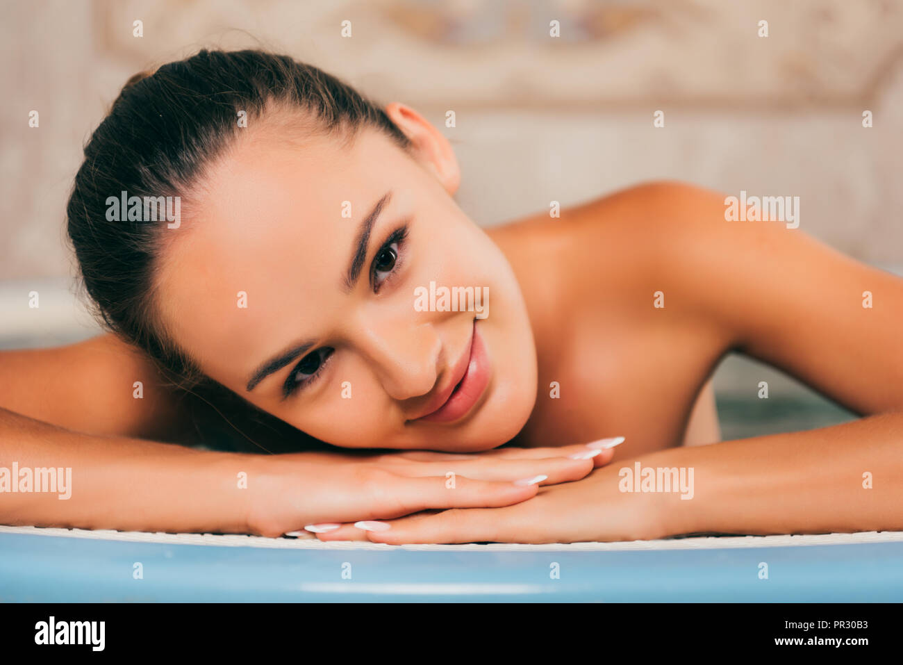 young woman resting at salon and looking at camera - Stock Image