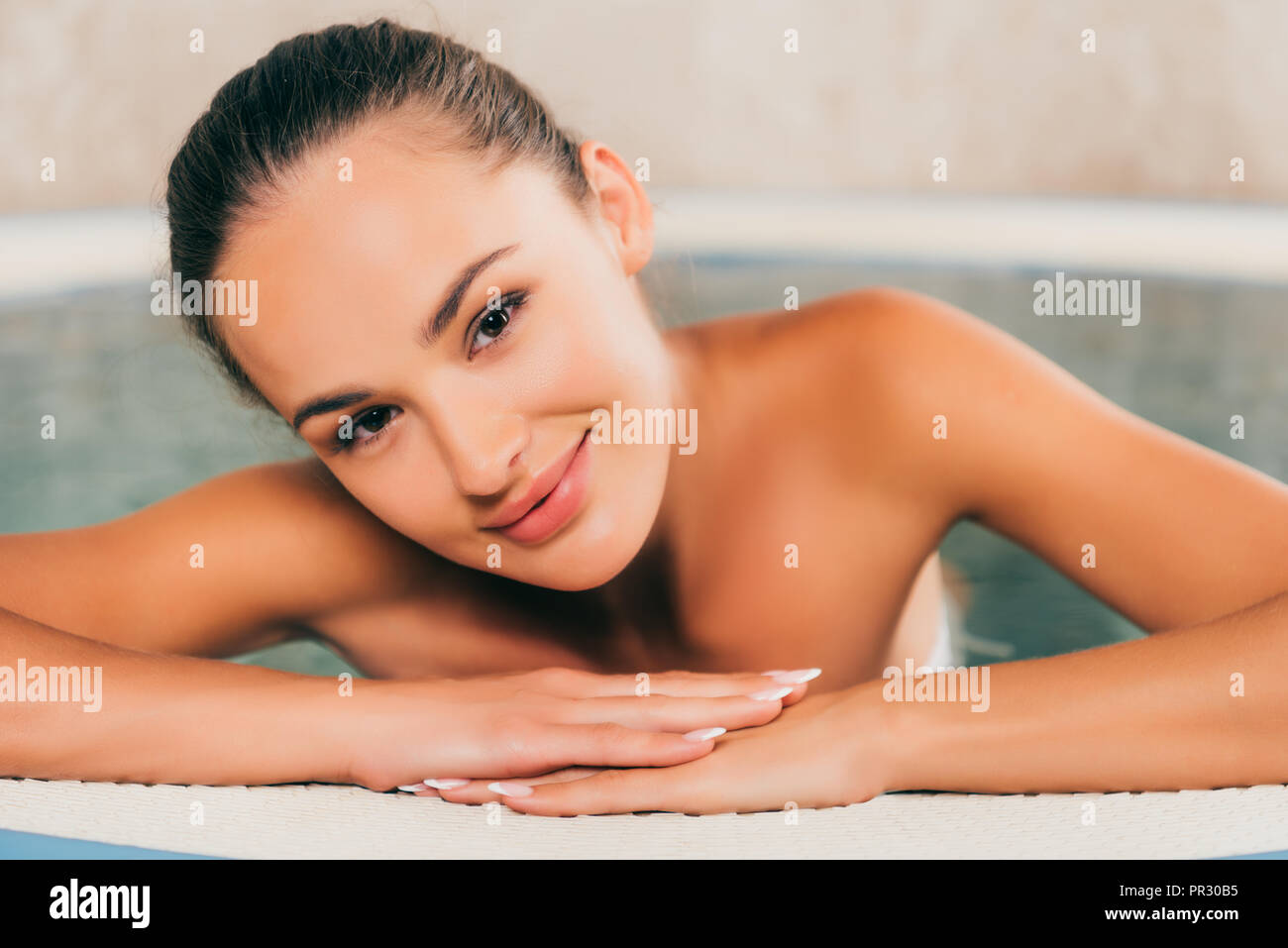 woman relaxing in swimming pool in spa salon and looking at camera - Stock Image