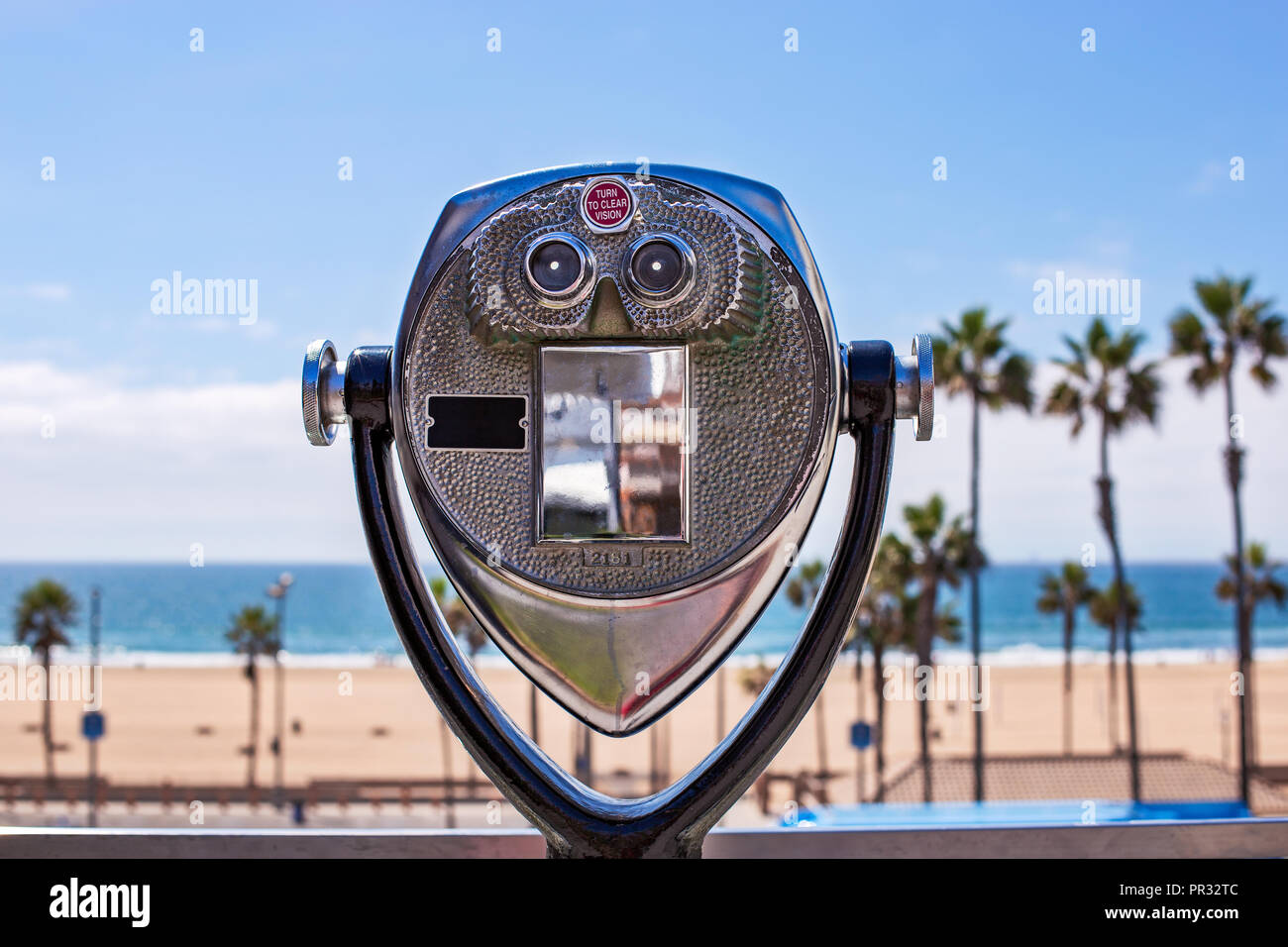 Coin operated binoculars looking out over a beach scene with palm trees, sand and the Pacific Ocean in Huntington Beach, California. - Stock Image