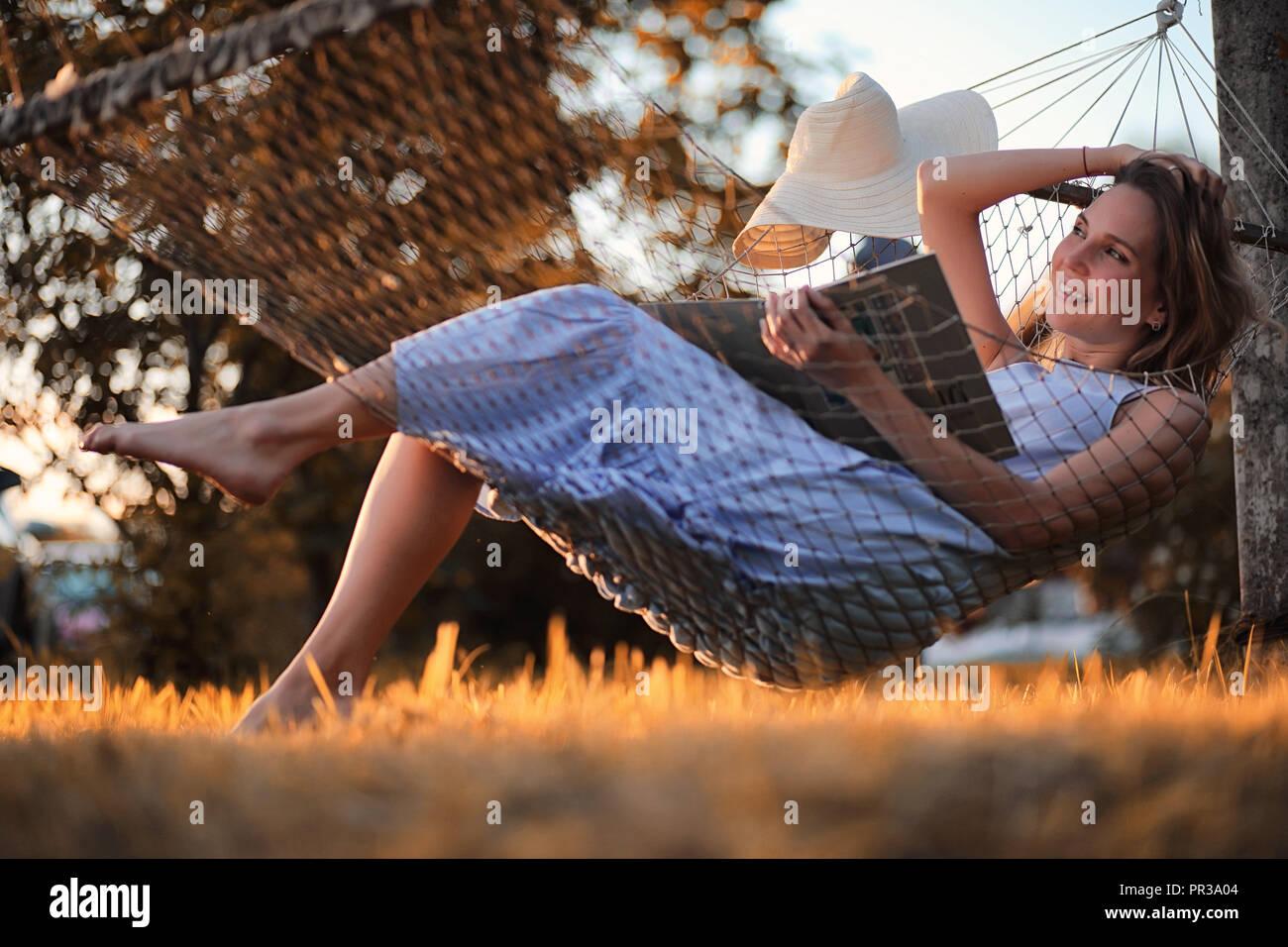 Beautiful girl in hammock reading a book  - Stock Image