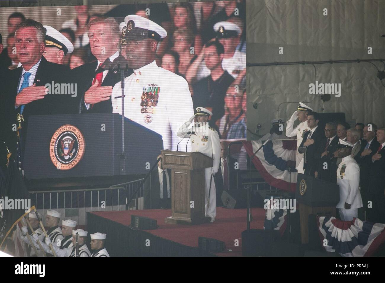 NORFOLK, Va. (July 22, 2017) -- Chief Yeoman Berwyn Tinnion, a USS Gerald R. Ford Sailor, sings the National Anthem during Ford's commissioning ceremony. Ford is the lead ship of the Ford-class aircraft carriers, and the first new U.S. aircraft carrier design in 40 years. - Stock Image