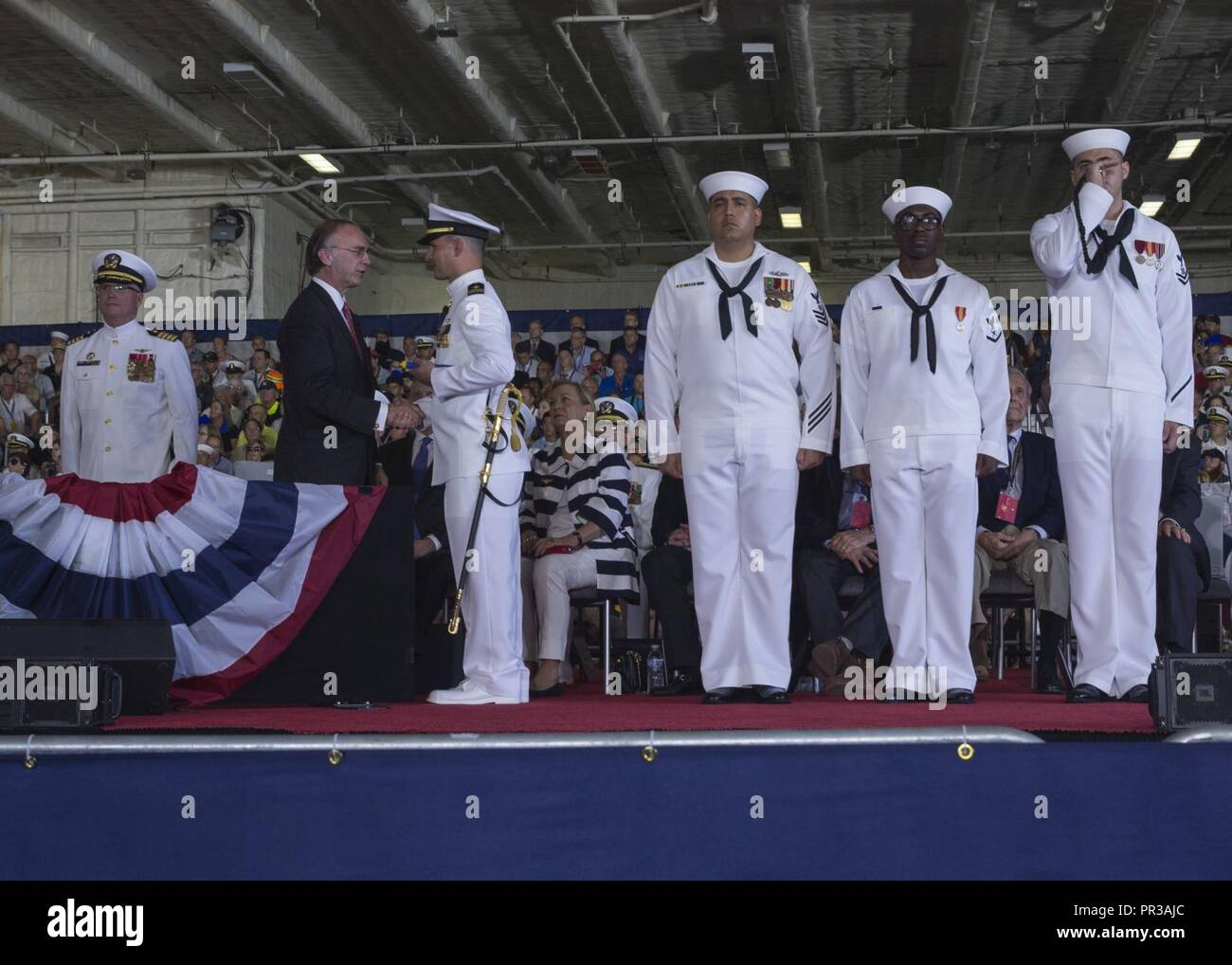 NORFOLK, Va. (July 22, 2017) -- Greg Willard, President of the Ford Foundation, passes a long glass to Lt. Joel Cincotta to assume the first watch onboard the newly commissioned USS Gerald R. Ford (CVN 78). Ford is the lead ship of the Ford-class aircraft carriers, and the first new U.S. aircraft carrier design in 40 years. - Stock Image