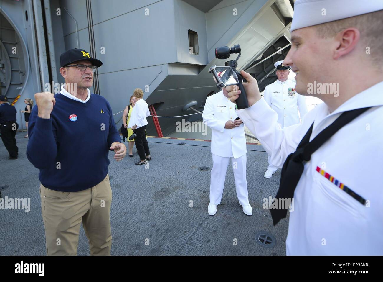 Va. (July 22, 2017) – Jim Harbough, head football coach at University of Michigan, records a video message for the crew of USS Gerald R. Ford (CVN 78) during the ship's commissioning ceremony at Naval Station Norfolk. Ford is the lead ship of the Ford-class aircraft carriers, and the first new U.S. aircraft carrier design in 40 years. - Stock Image