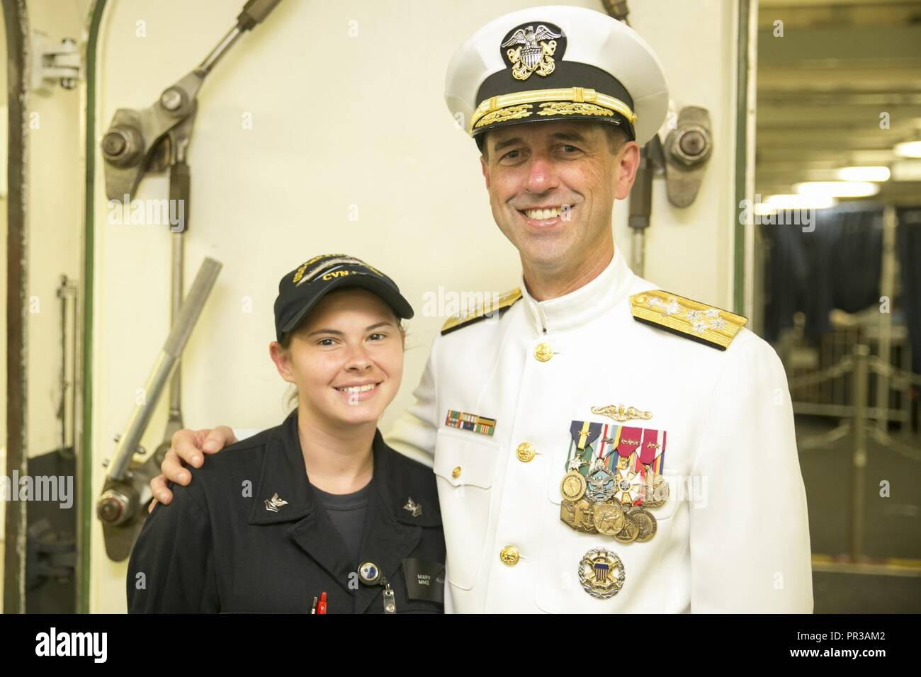 Va. (July 22, 2017) – Chief of Naval Operations Adm. John Richardson and Machinist Mate 2nd Class Mary Allinder, assigned to USS Gerald R. Ford (CVN 78), pose for a photo during Ford's commissioning ceremony at Naval Station Norfolk. Ford is the lead ship of the Ford-class aircraft carriers, and the first new U.S. aircraft carrier design in 40 years. - Stock Image