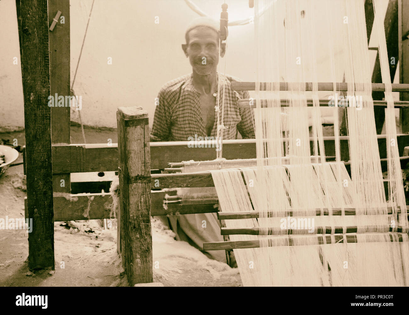 Majdel village & its primitive weaving. A native weaving establishment, closer. Photograph shows a man working at a loom - Stock Image