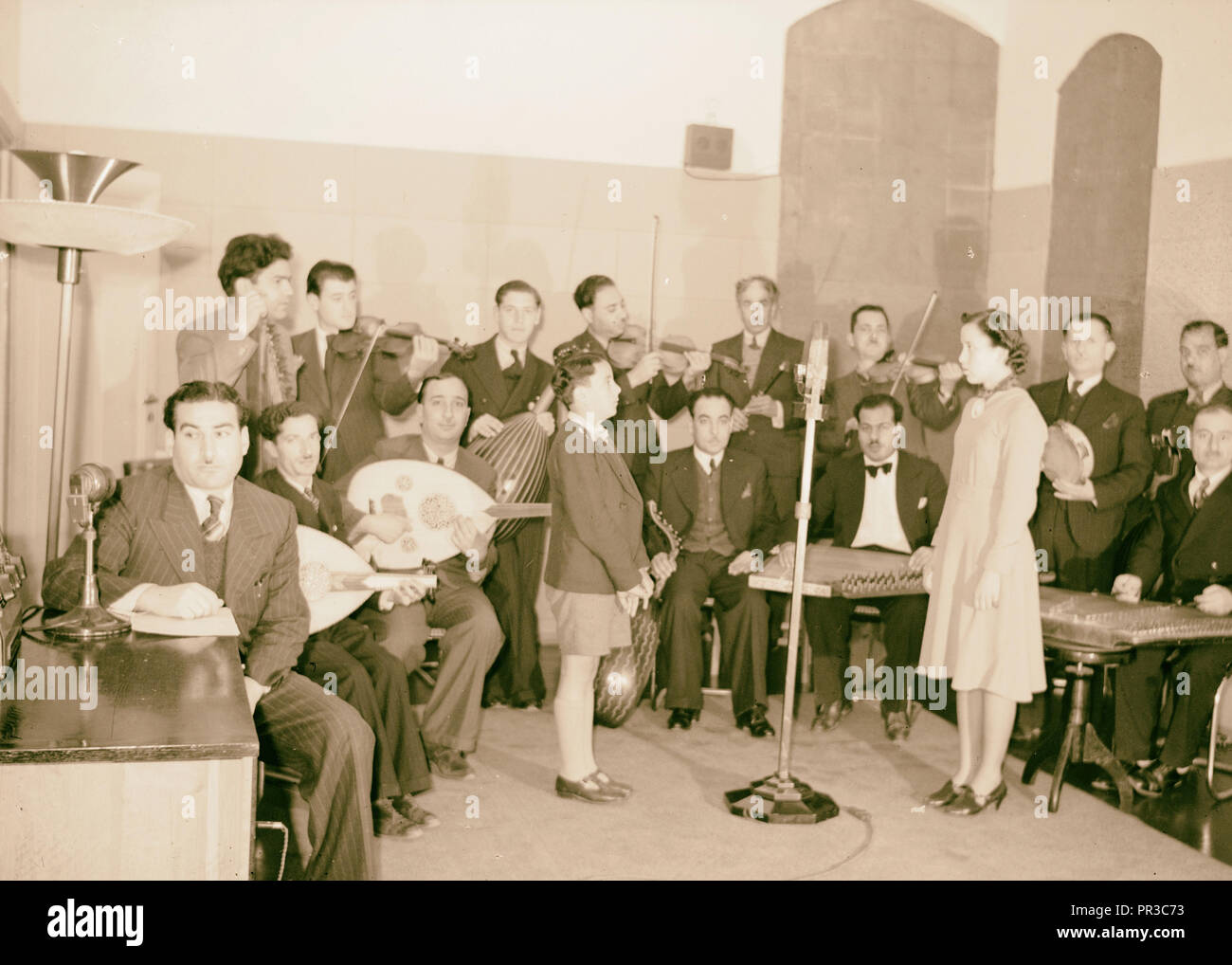 Broadcasting. Palestine Broadcasting Service. Arab musicians with girl & boy soloists at microphone. 1940 - Stock Image