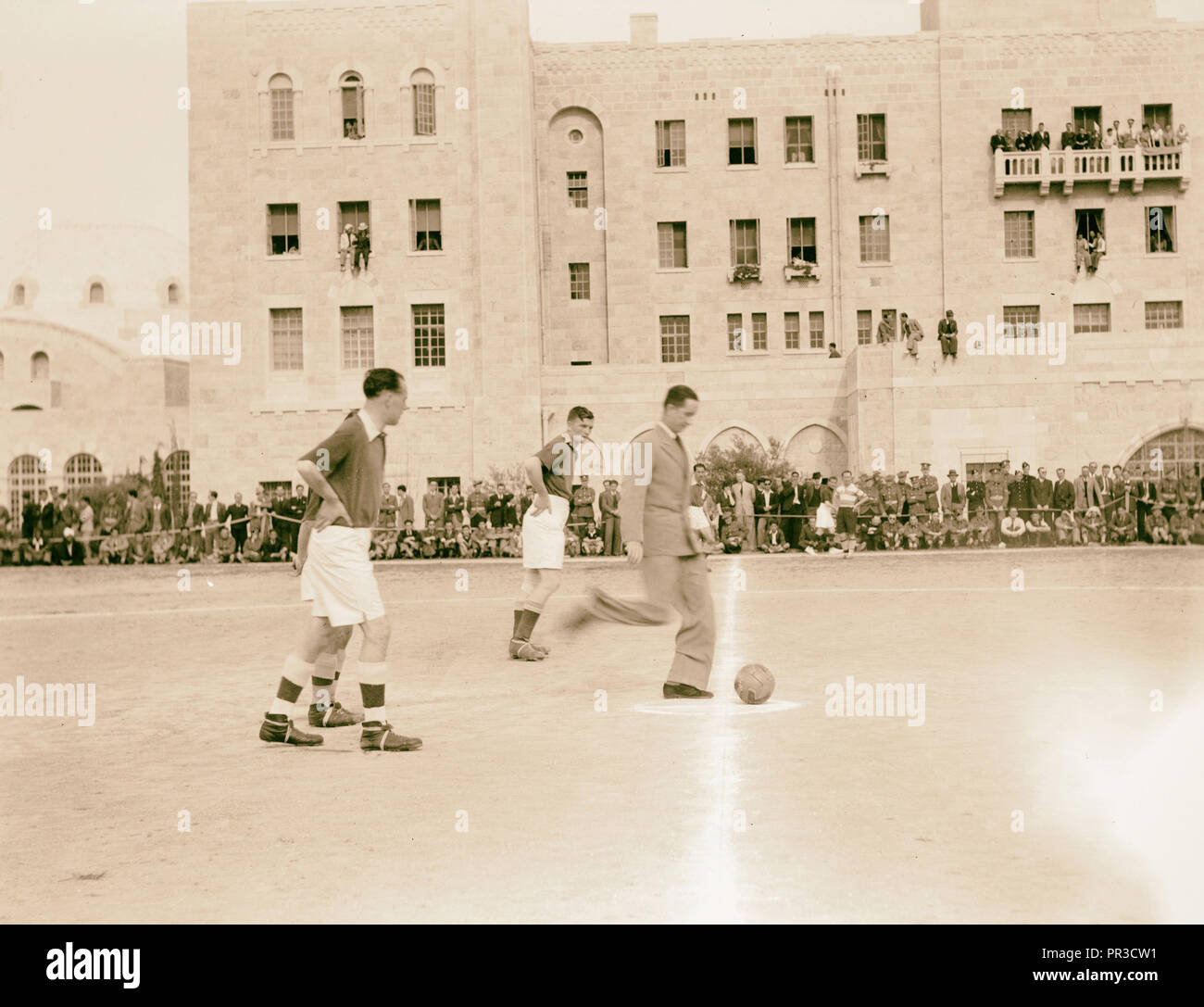 Football game 'Y' versus British Army. Mr. Macphearson, chief secretary 'kicking off' the ball, Middle East - Stock Image