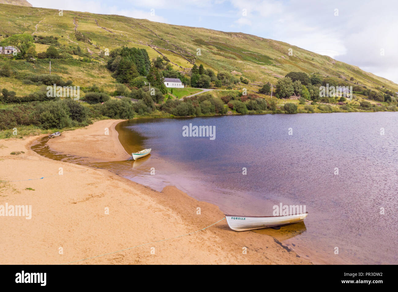 An aerial view of two boats on the beach at scenic Lough Nafooey in the Connemara region of Ireland. Stock Photo