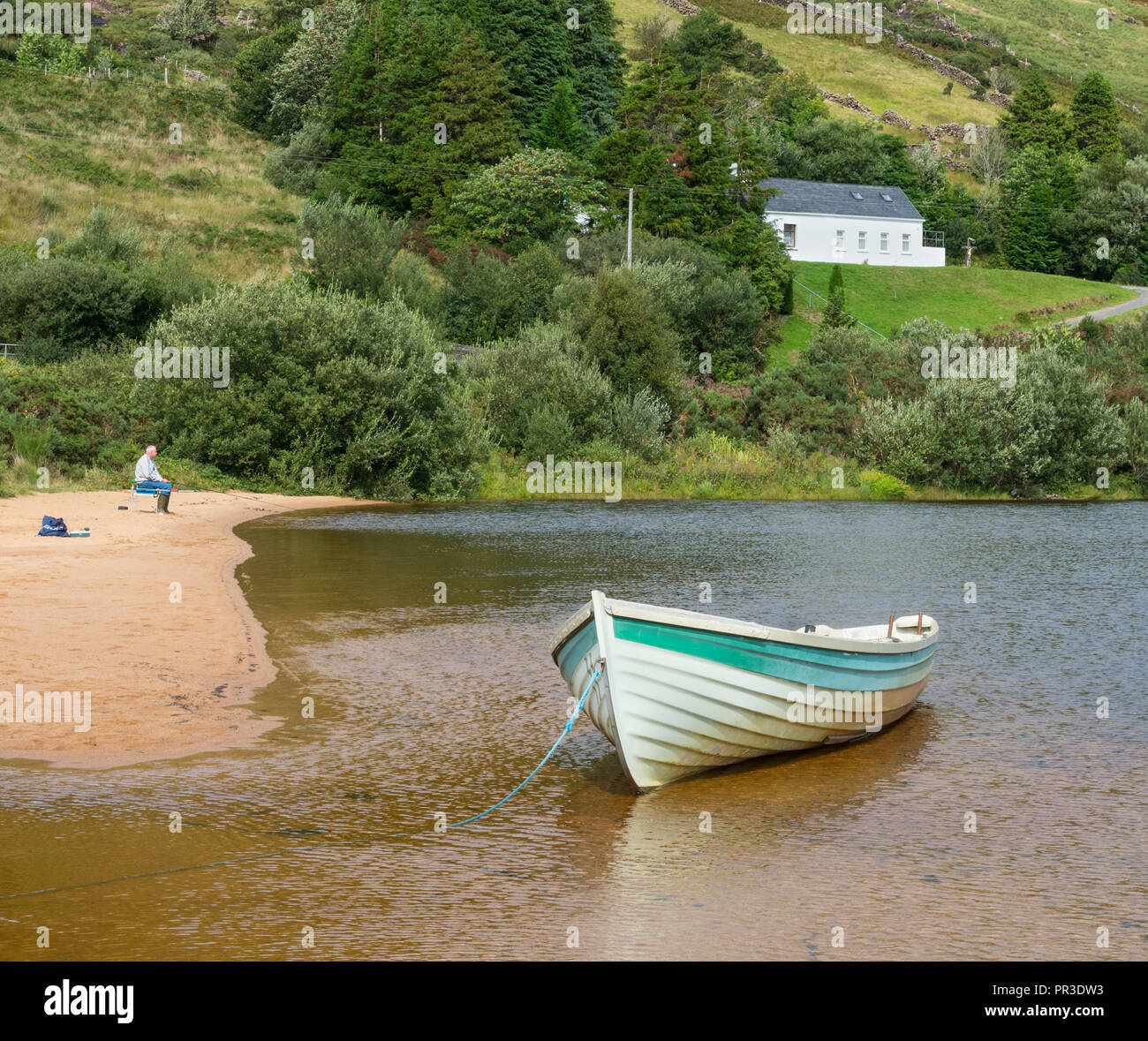 A lone fisherman and a boat on the beach at Lough Nafooey in the Connemara region of County Galway in Ireland. Stock Photo