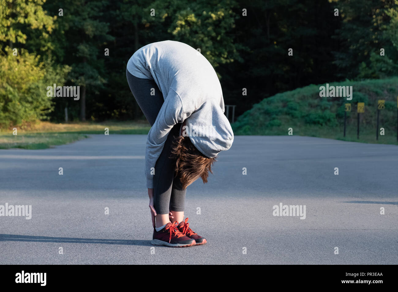 Woman doing beginner yoga excercise for stretching at park. Female person stretching before jogging outdoors - Stock Image