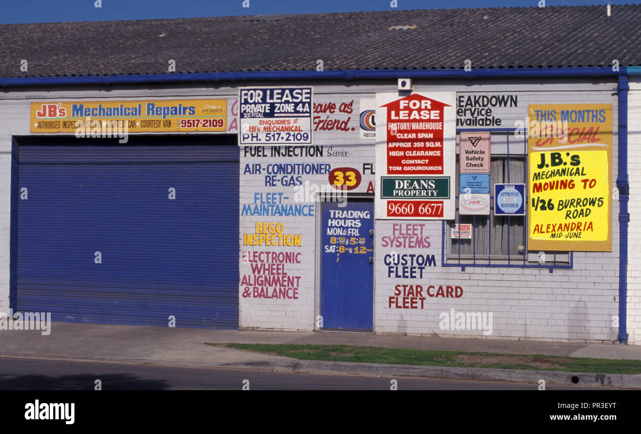 'FOR LEASE' AND ASSORTED SIGNS ON A BUILDING ONCE USED AS A GARAGE, ALEXANDRIA, INNER SYDNEY, NSW, AUSTRALIA Stock Photo