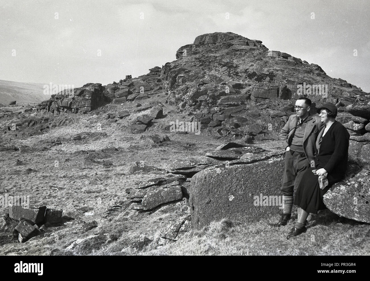 1930s, historical, a couple resting taking in the view at Longaford Tor, a hillside rocky peak or ridge at Dartmoor national park in Devon, England, UK, a natural wild open moorland that contains many ancient rock formations or granite outcrops known as tors. - Stock Image