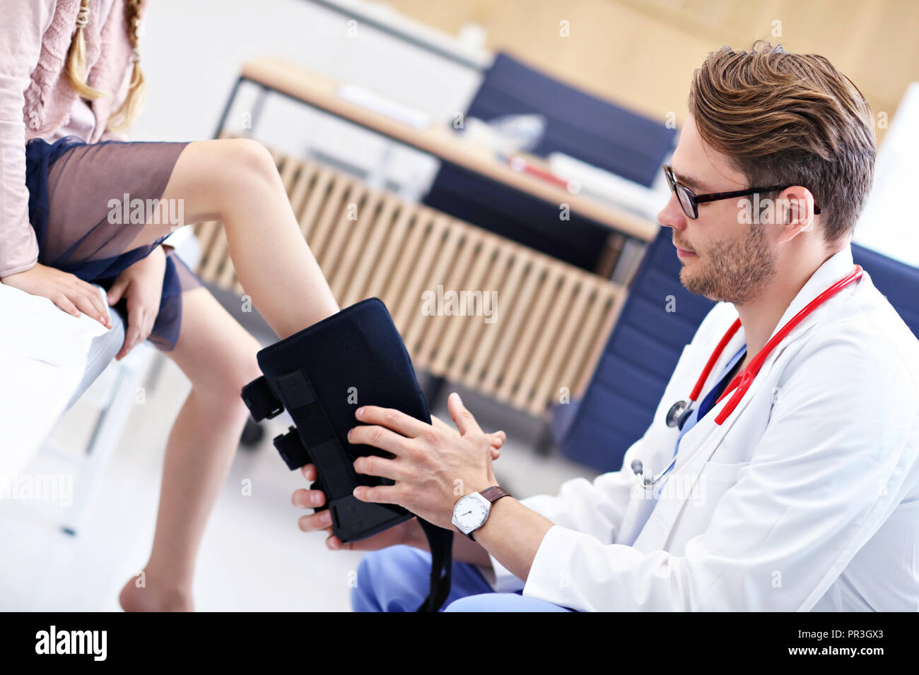 Little girl in clinic having a checkup with orthopaedist - Stock Image