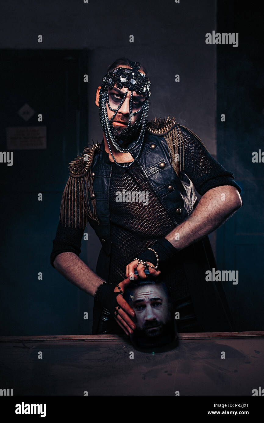 The man in leather cloak with ornamentals on his head opening the jar with a head of a man. Brutal dark style - Stock Image