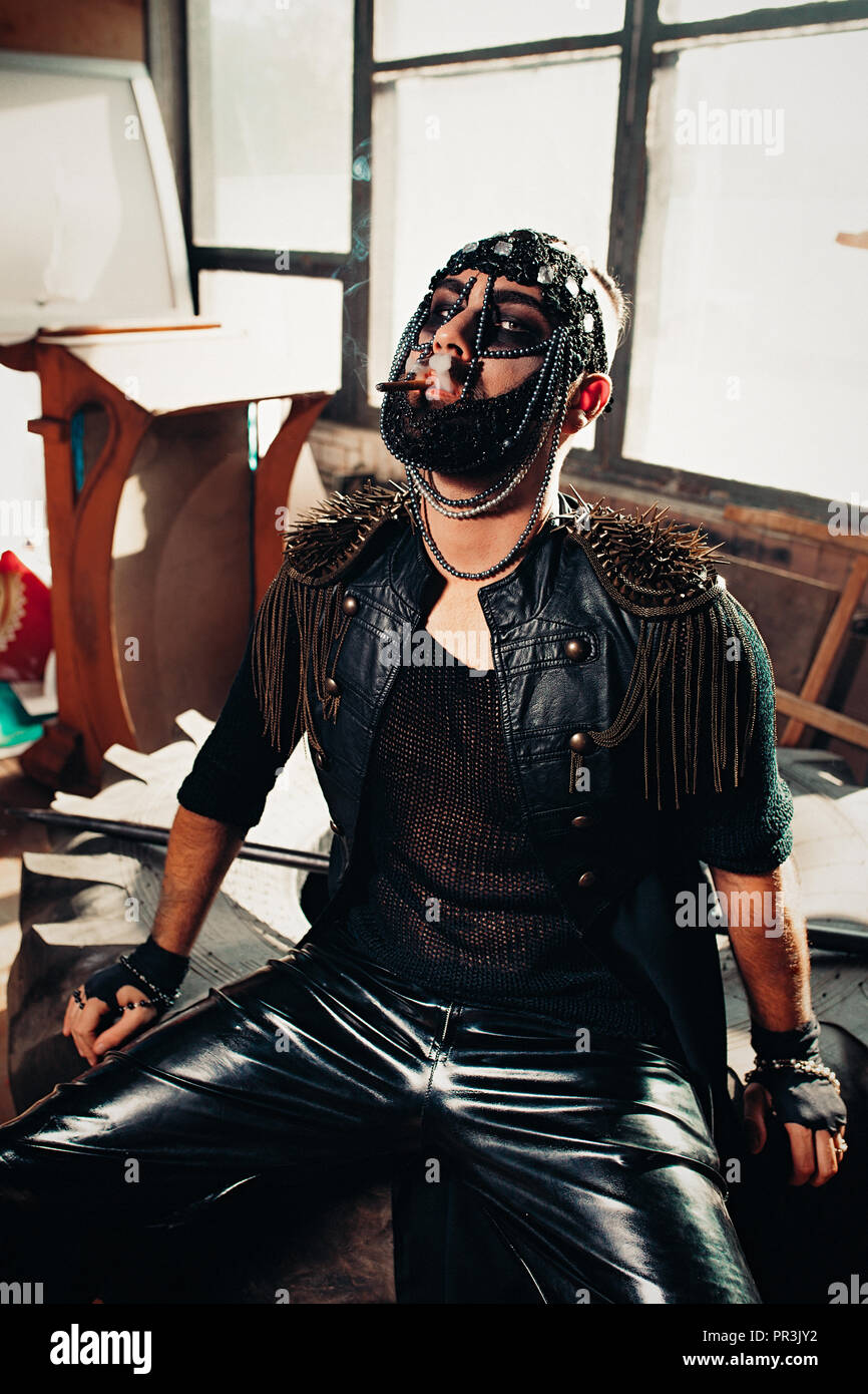 The man in a leather cloak with spikes and leather trousers with ornamentals on his head smoking a cigarette indoors. Brutal dark style - Stock Image