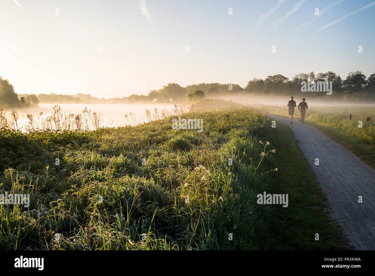 Early morning runners. Two people running alongside the River Trent, Nottinghamshire, England, UK - Stock Image