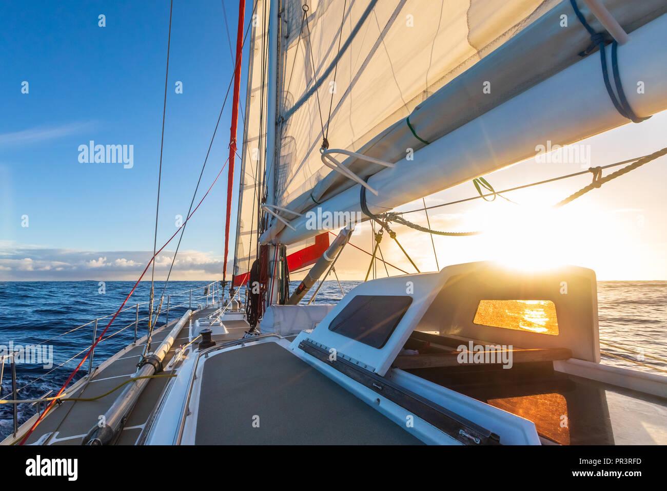 Sailing on sailboat yacht with beautiful sunset light clear blue sky and flat sea in drake passage, summer cruising, closeup of boat deck - Stock Image