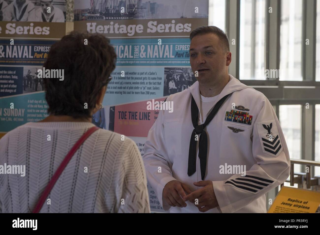 ST. PAUL, Minn. (July 22, 2017) – Mass Communication Specialist 1st Class Clifford L. H. Davis, assigned to the Naval History and Heritage Command, discusses Naval heritage and history with visitors of the Minnesota Historical Society during Minneapolis/St. Paul Navy Week. Navy Week programs serve as the Navy's principal outreach effort into areas of the country without a significant Navy presence, with 195 Navy Weeks held in 71 different U.S. cities. Stock Photo