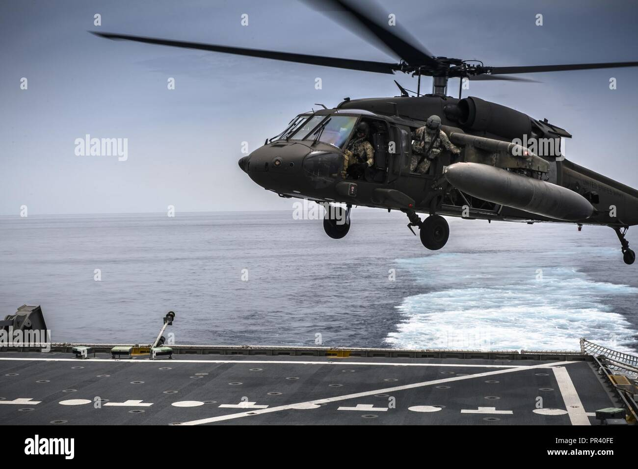 U.S. Army UH-60 Blackhawk from 1-228th Aviation Regiment Charlie Company conduct deck landing qualification aboard the USNS Spearhead off the coast of Honduras in the Caribbean Sea, July 27, 2017. The 1-228th C-Company deck landing qualification consisted of classroom instruction and 5 landings with an Instructor Pilot. Once qualified each Pilot will need to maintain their currency on a scheduled timeline. Stock Photo