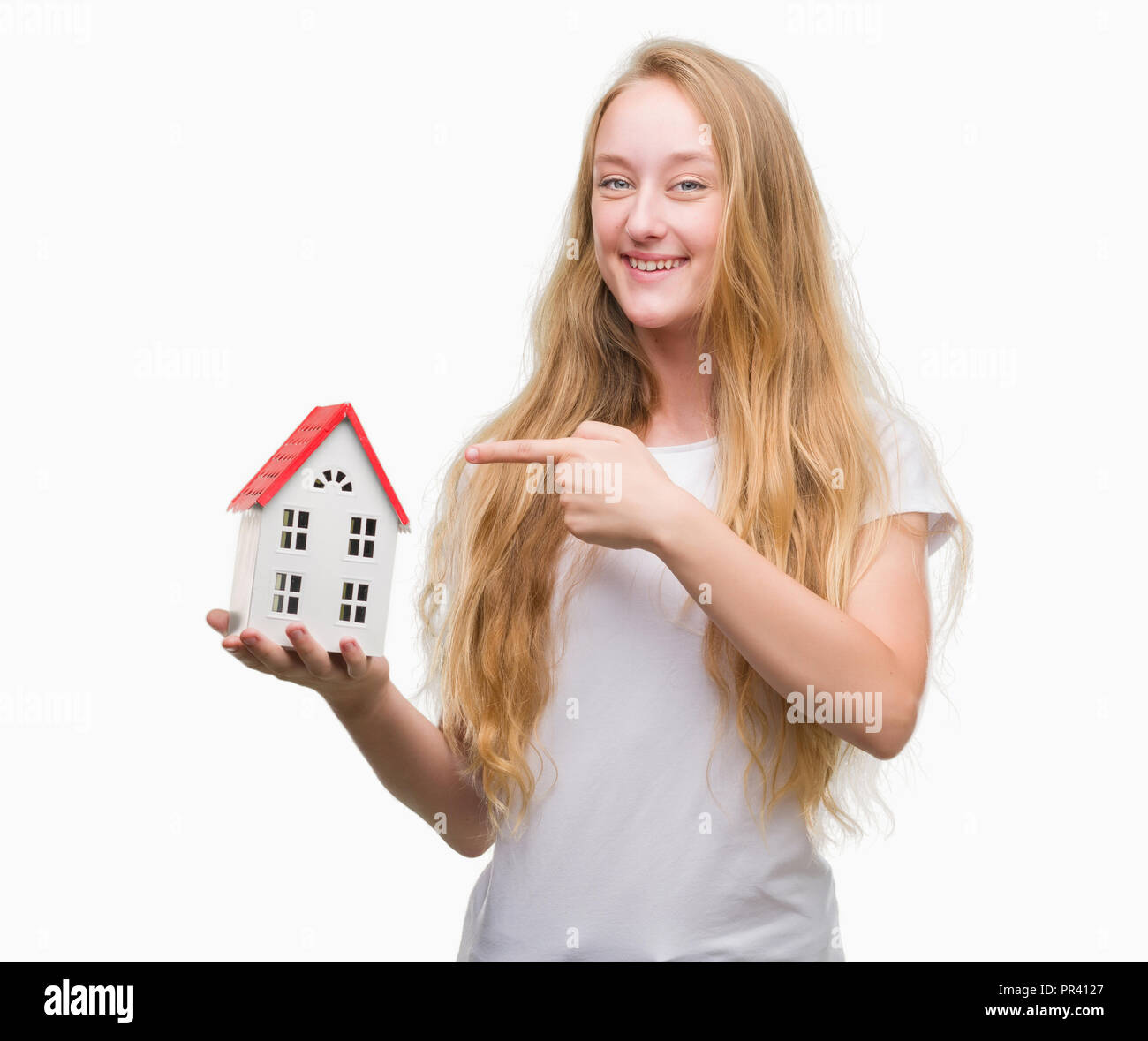 Blonde teenager woman holding family house very happy pointing with hand and finger - Stock Image