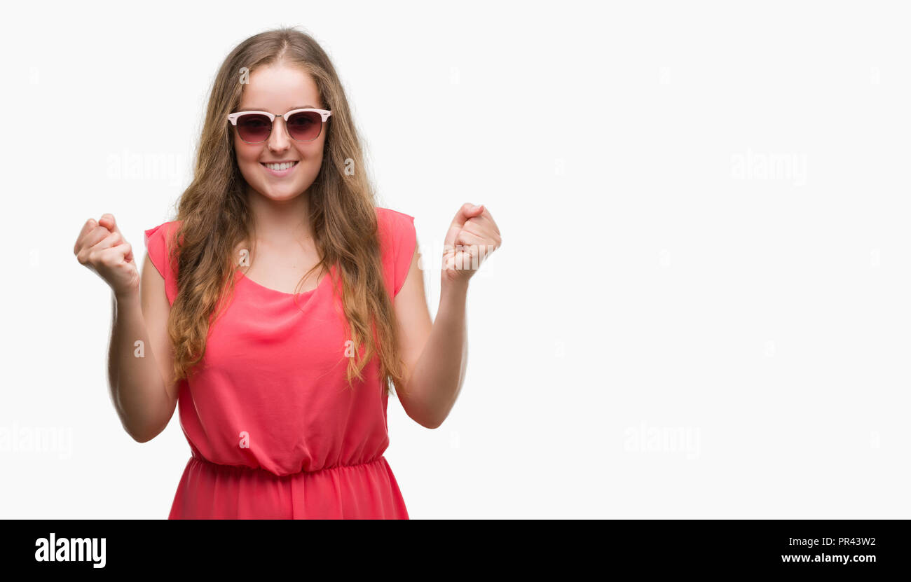 Young blonde woman wearing pink sunglasses screaming proud and celebrating victory and success very excited, cheering emotion - Stock Image